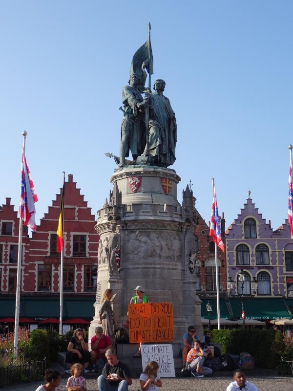 Statue der historischen Aufrührer Breydel und de Coninck auf dem Marktplatz von Brügge, im Hintergrund eine Häuserzeile, unter der Statue Menschen, die für den Klimaschutz demonstrieren.