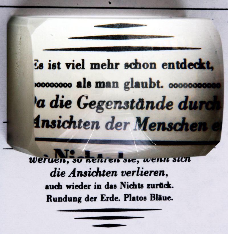 Ein Lesestein, der Schrift vergrößert (um 1900).